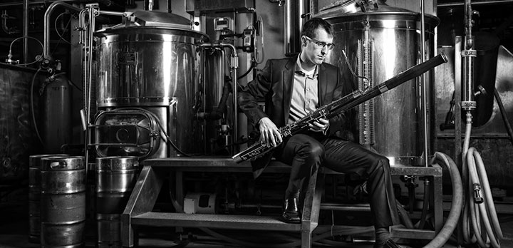 CSO musician Chris Sales holding his bassoon at a brewery