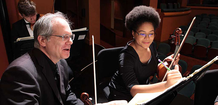 CSO musician teaching a youth orchestra member