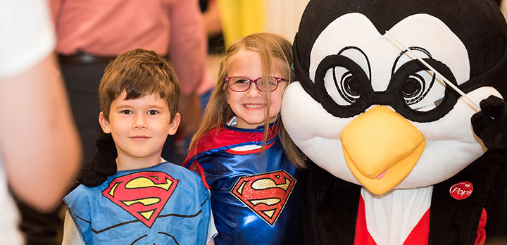 Pops mascot Tempo the Penguin poses with two young children