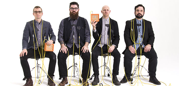 Photo of So Percussion artists sitting in chairs with wires on and around them
