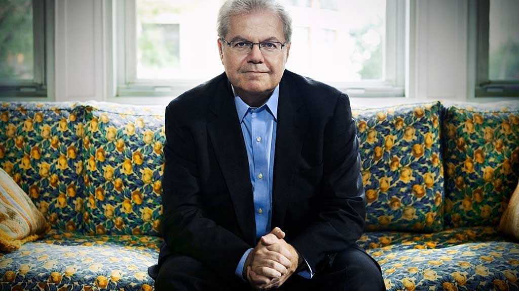 Headshot of pianist Emanuel Ax on a bright couch