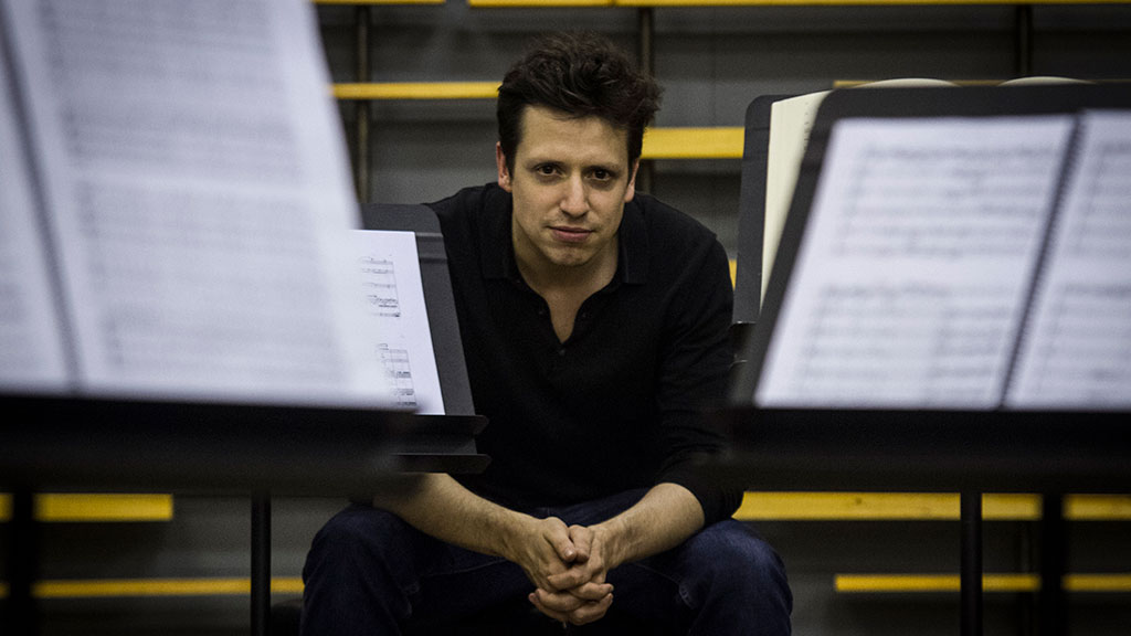 Conductor Paolo Bortolameolli sits with music stands