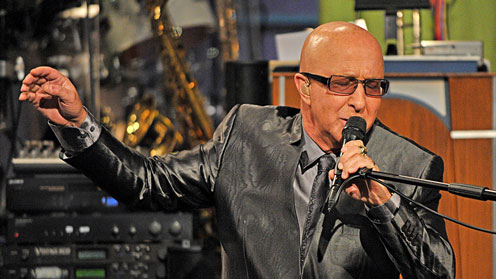 Paul Shaffer of Late Night singing into a mic