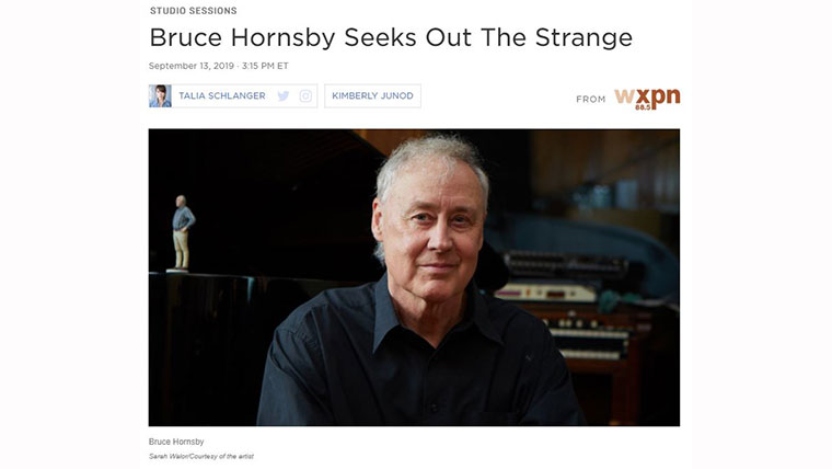 Bruce Hornsby sitting in front of a piano