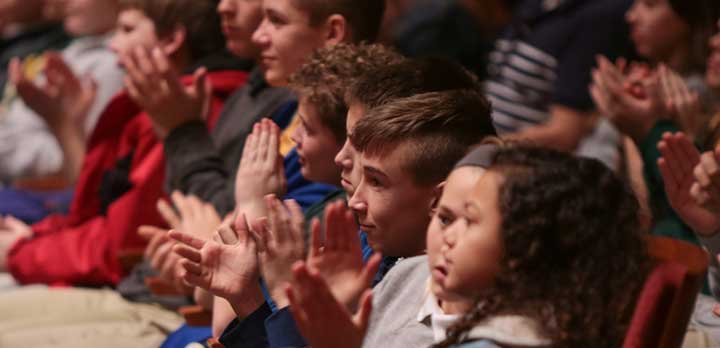 A handful of young audience members applaud during a concert