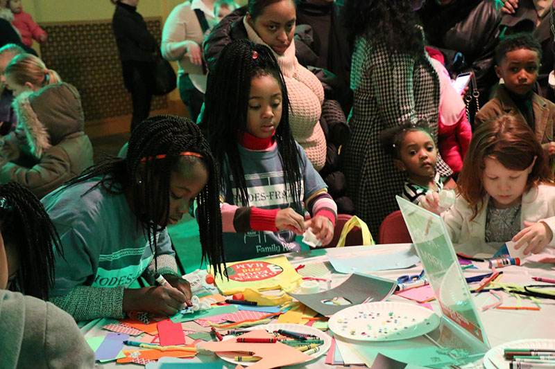 Families enjoying arts and crafts at the Family Fun Zone before a concert