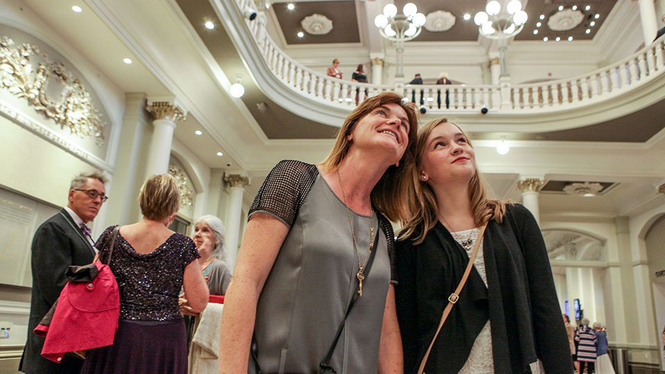 A mother and her daughter marveling at the Music Hall foyer